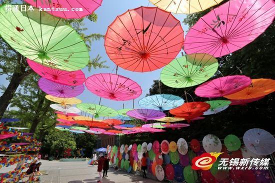 """昨天,游客在运河公园欣赏油纸伞。当日是""""五一""""小长假第一天,锡城天气晴好,市民们纷纷走出家门享受大好春光。 商报记者宦玮 摄"""