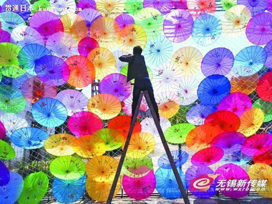 """宜兴市玉龙潭风景区首届油纸伞文化节于""""五一""""小长假开幕。图为4月28日工作人员正在紧张忙碌地准备着。(无锡日报)"""
