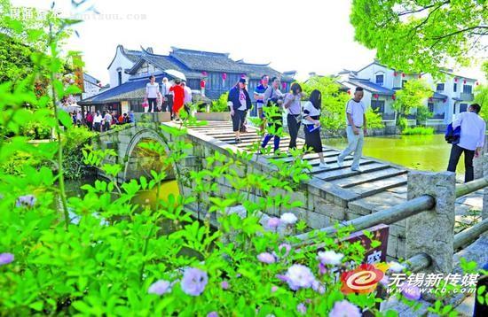 """昨天是""""五一""""小长假的首日,天气晴好,市民纷纷选择出游休闲。图为游客在太湖新城巡塘古镇游玩。(无锡日报)"""